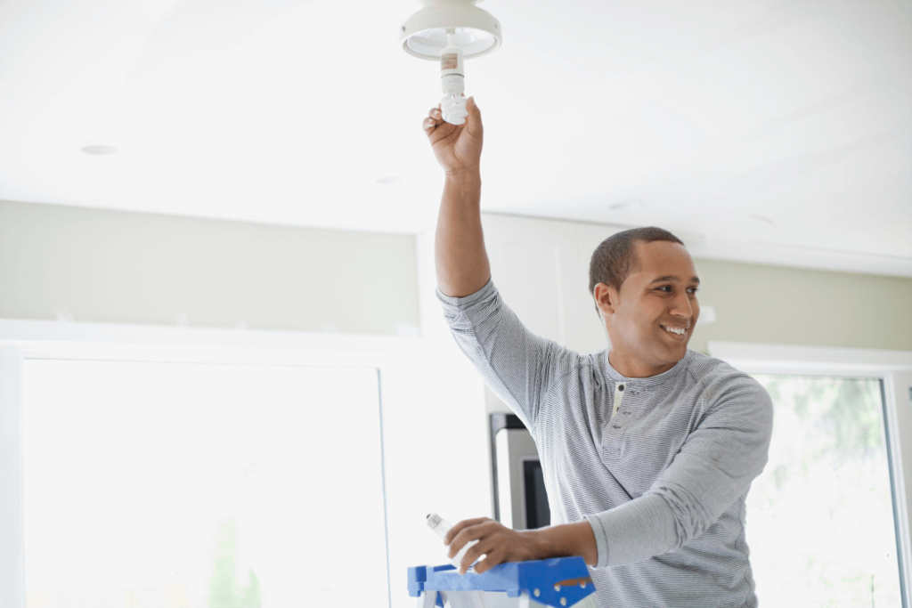 tips to save on electric costs during summer man changing light bulb
